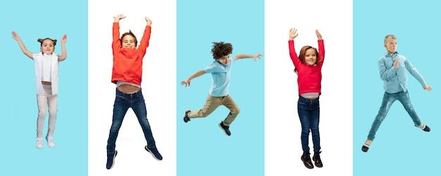 초등학교 아이들이나 학생들은 바이컬러 스튜디오 배경에서 화려한 캐주얼 옷을 입고 점프합니다. 창의적인 콜라주. 학교, 교육, 어린 시절 개념으로 돌아가십시오. 쾌활한 소녀와 소년.