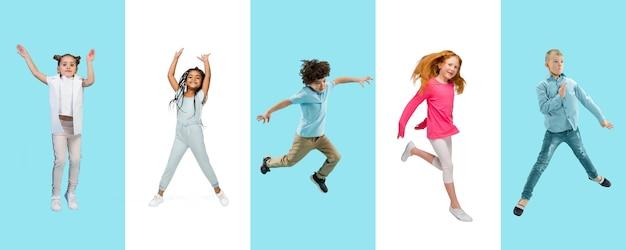 二色のスタジオの背景にカラフルなカジュアルな服を着てジャンプする小学生や生徒のグループ。クリエイティブなコラージュ。学校に戻る、教育、子供の頃の概念。陽気な女の子と男の子。