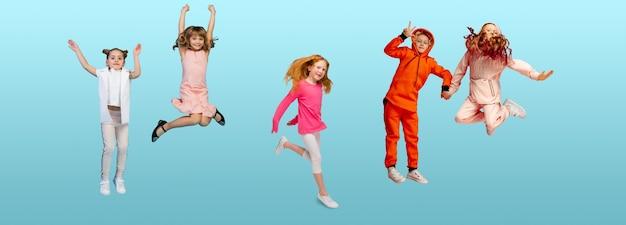 青いスタジオの背景にカラフルなカジュアルな服を着てジャンプする小学生や生徒のグループ。クリエイティブなコラージュ。学校に戻る、教育、子供の頃の概念。陽気な女の子と男の子。