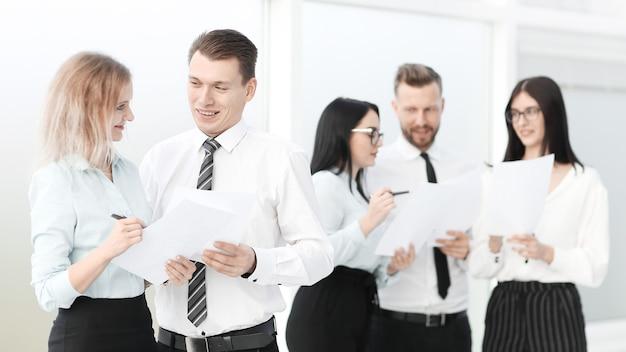 会議の前にオフィスのロビーに立っている従業員のグループ。ビジネスコンセプト