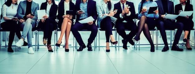Группа сотрудников, использующих свои устройства в конференц-зале. фото с копией пространства