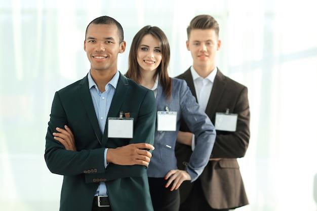 Группа сотрудников с пустыми значками, стоящих друг за другом в офисе