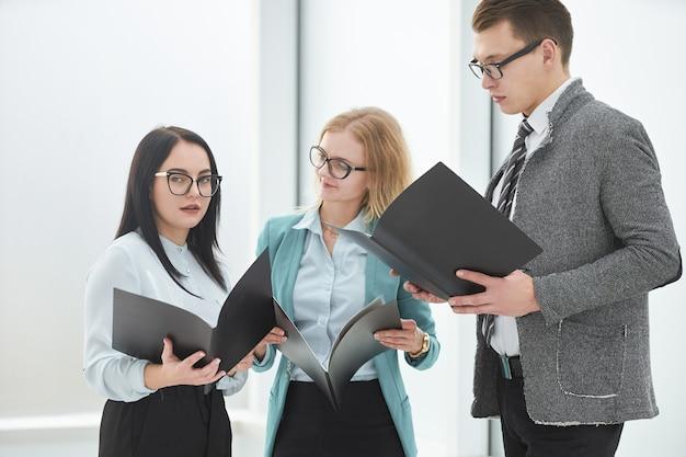 Группа сотрудников с деловым документом, стоящим в офисе. бизнес-концепция
