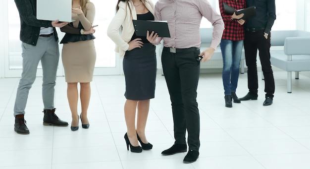 オフィスで会う前にラップトップとクリップボードを持っている従業員のグループ