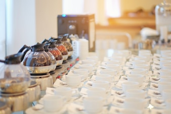 Group of empty Many rows of white ceramic coffee or tea cups and spoons on glass table