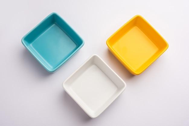 白または灰色の表面上に分離された空の白、黄、青のセラミックサービングボウルのグループ