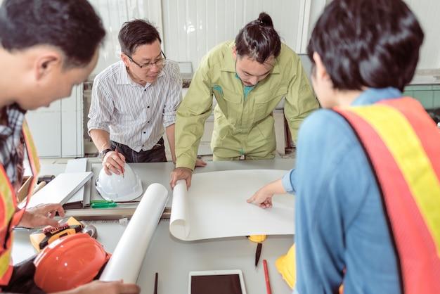Группа инженеров и рабочих совещание по рисованию. работа с партнерскими и инженерными инструментами на рабочем месте
