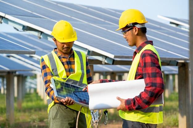 태양 광 발전소, 일상적인 녹색 에너지 혁신을위한 태양 광 발전소, 태양 광 발전소의 운영 및 유지 보수에서 태양 전지 패널을 검사하는 엔지니어 그룹.