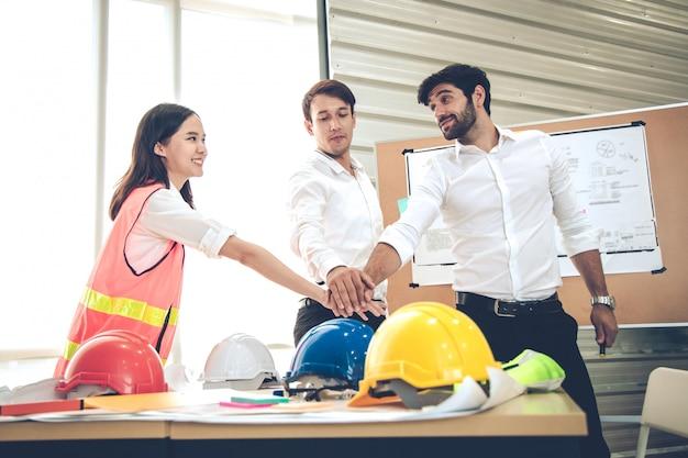 Группа в составе инженеры с соединяет руку совместно в концепции сыгранности.
