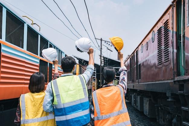 Группа рабочих-инженеров, держащая каску после окончания большого проекта между зазором поездов