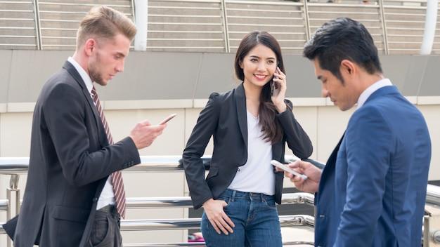 Группа предпринимателей людей использует мобильный телефон смарт-смотреть. молодые красивые деловые люди носят платье строго элегантного костюма.