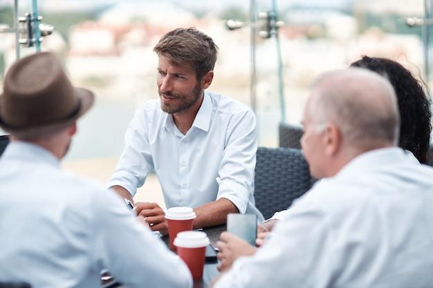 ディスカッションテーブルに座って共同プロジェクトについて話し合う起業家のグループ