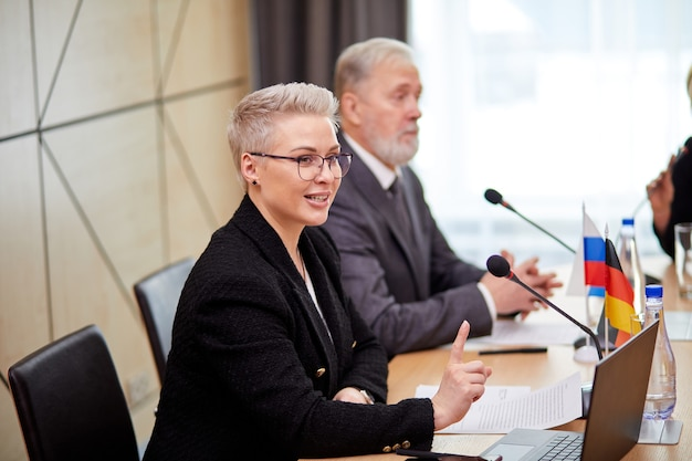 Группа европейских руководителей обсуждает план на будущее в современном офисном здании стартапа, одетые в формальную одежду, сидят вместе, используя микрофон для выступления