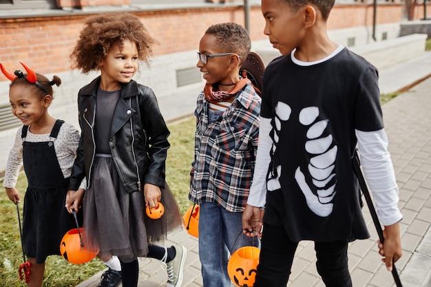 야외에서 할로윈 의상을 입고 장난을 치거나 치료를 하는 흥분한 아프리카계 미국인 어린이 그룹