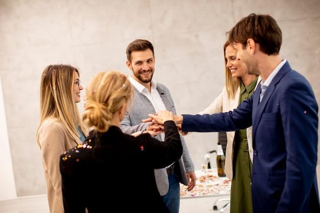 Группа возбужденных деловых людей празднует и тосты с конфетти, падающими в офисе