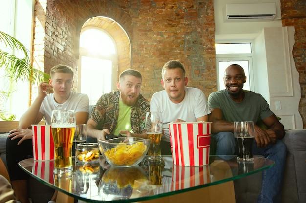집에서 비디오 게임을하는 흥분된 친구의 그룹입니다. 남성 게이머 또는 팬이 집에서 시간을 보내고 함께 즐거운 시간을 보내는 경우