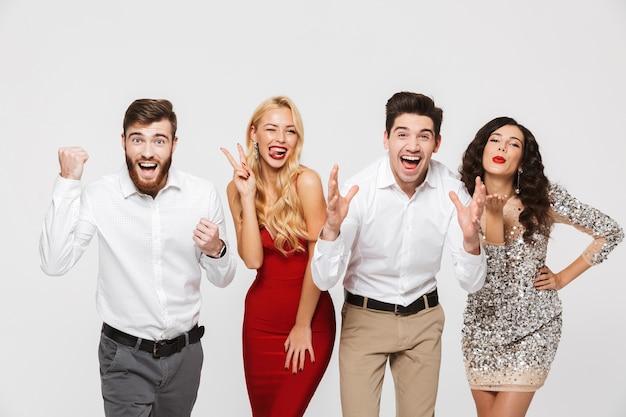 Группа возбужденных, умных одетых друзей, стоящих изолированно над белой, празднует новый год