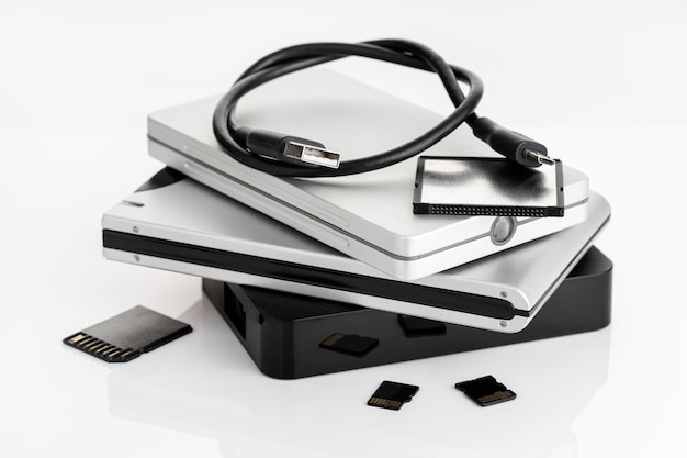 Группа внешних жестких дисков и карт памяти на белом столе. концепция хранения данных