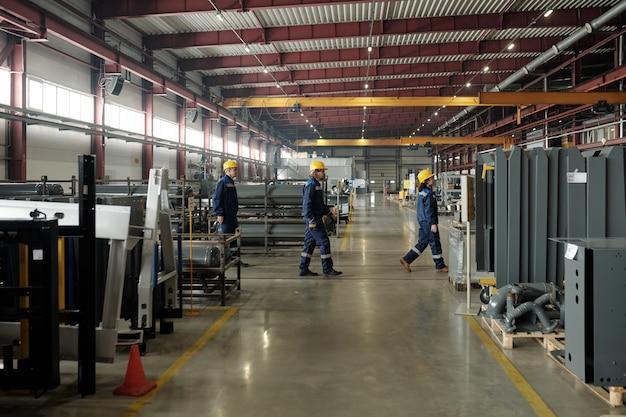 산업의 압축기 장치 사이를 걷고 있는 안전모와 파란색 작업복을 입은 공장 직원 그룹