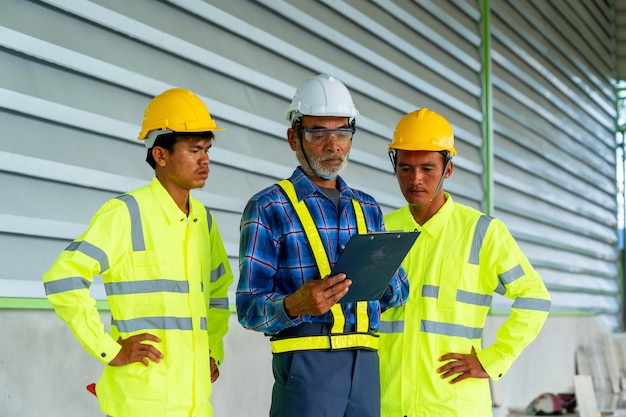 Группа заводских рабочих разговаривает при проверке промышленного объекта