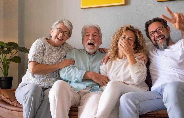 Группа семьи, отдыхая на диване у себя дома, весело и смеясь. красивые люди, родители и взрослые сыновья, два поколения смотрят в камеру