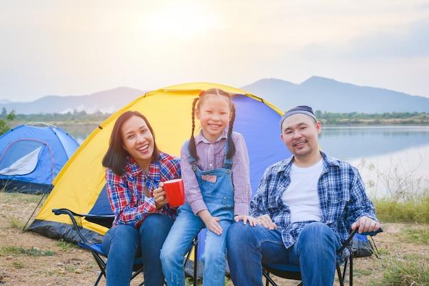 Группа семейного путешествия и кемпинга на берегу озера в лесу, сидя все вместе и улыбаются