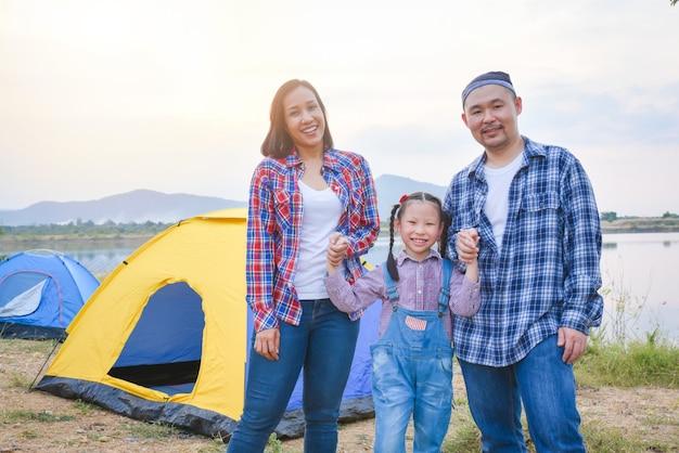 Группа семейного путешествия и кемпинга на берегу озера в лесу, стоя все вместе и улыбаюсь