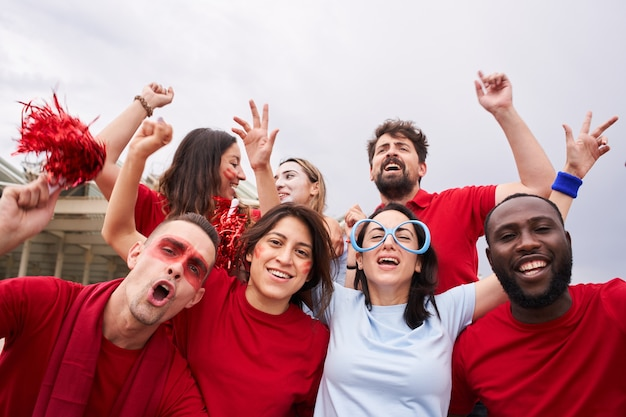 相手チームのファンと赤いシャツを着たスタンドのサッカーチームのファンのグループ