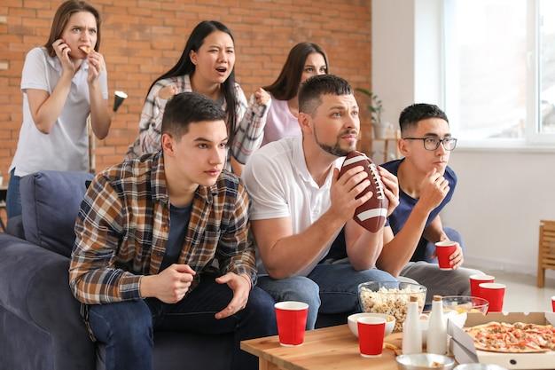 テレビでラグビーを見ているファンのグループ