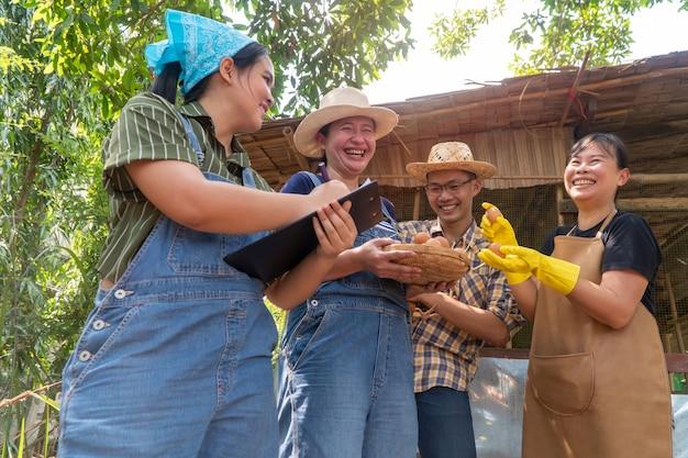 닭 농장 옆에 서서 웃고 있는 농부들. 농장에서 생산된 제품에 만족하기 때문에 모두 웃고 있습니다. 무독성 식품의 개념