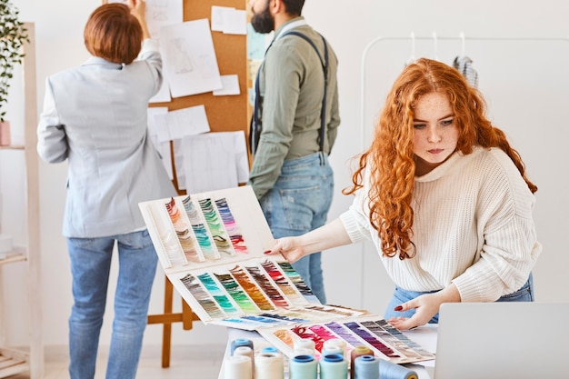 アイデアボードとカラーパレットでアトリエで働くファッションデザイナーのグループ
