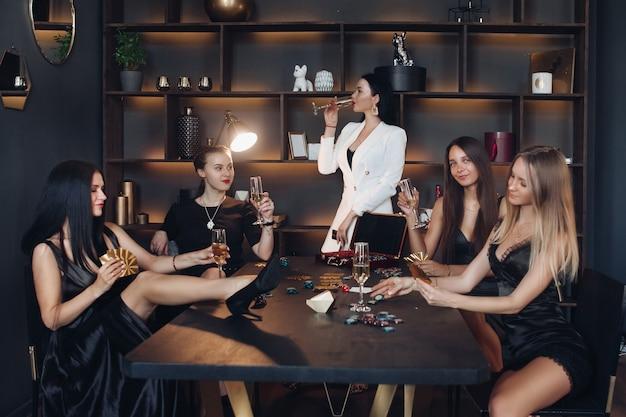 Группа в составе молодая сексуальная женщина моды наслаждаясь игрой в покер и выпивая среднюю длинную съемку шампанского.