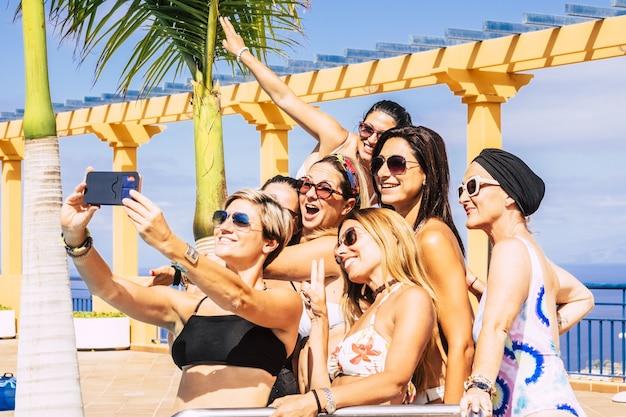 리조트에서 여름 휴가를 즐기고 스마트폰으로 셀카를 찍는 여성 친구들. 수영장 파티를 즐기는 수영복 여성. 휴대 전화 카메라를 사용하여 사진을 찍는 매력적인 여자 친구
