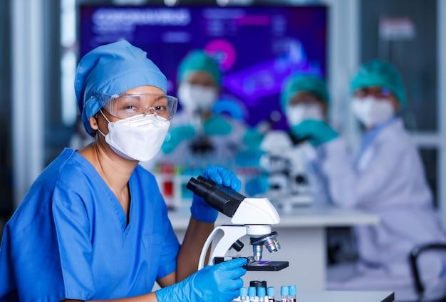 女性研究者チームのグループは、試験管とビーカーの間の実験室で顕微鏡と実験装置を扱うことに集中しました。 covid-19の発生における科学者の厳しい義務の概念。