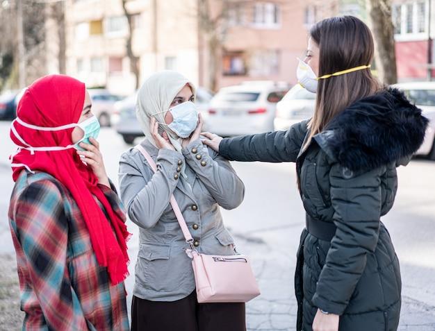 公害に対するマスクが付いている通りの女性のグループ