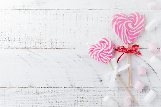 白い木製の背景にハートの形でお祝いの様々なキャンディーのグループ