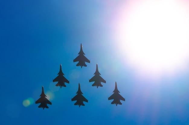 戦闘機の飛行機の太陽のグループは青い空を輝かせます。