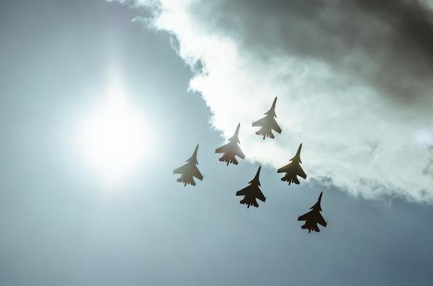 紫の日差しの中、空に浮かぶ戦闘機のグループが光りました。