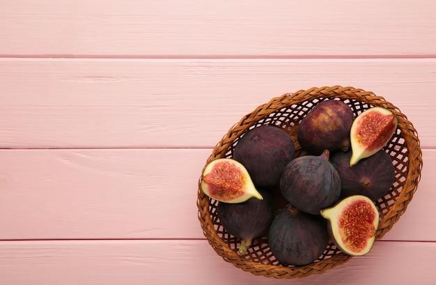 분홍색 배경에 나무 그릇에 무화과의 그룹입니다. 세로 사진입니다.