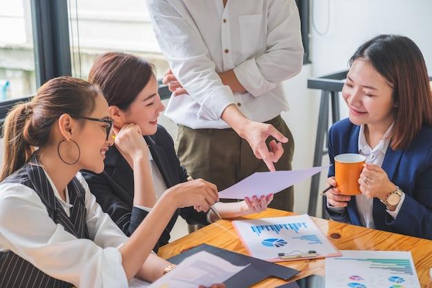 会議中に財務文書を分析するビジネスカジュアルの財務チームのグループ