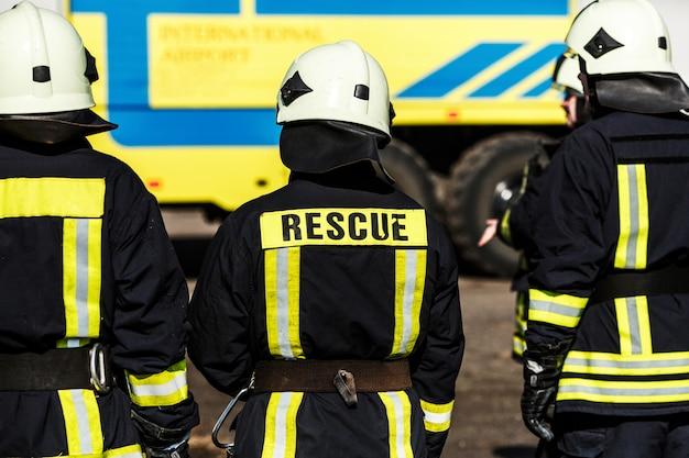 安全なヘルメットと車で制服立っている消防士のグループ