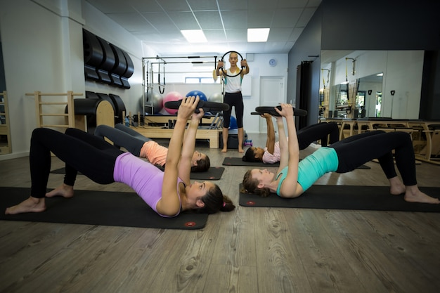 Группа подходящих женщин, тренирующихся с кольцом для пилатеса