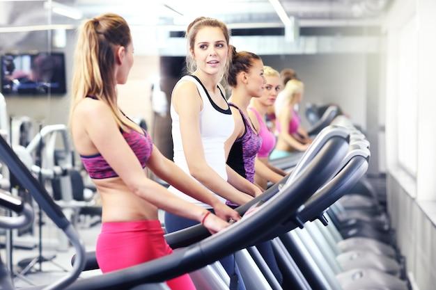 ジムでトレッドミルで運動している健康な女性のグループ