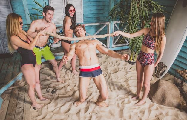 彼らの夏のビーチハウスで祝っている5人の友人のグループ