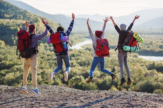 5人の幸せな友人のグループは日没時にジャンプします