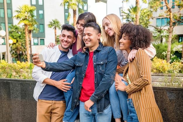 街の通りで携帯電話で自分撮りをしている5人の幸せな多文化の友人のグループは、カメラに向かってポーズをとって笑ったり笑ったりします