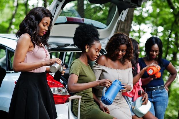 車に座っている5人の幸せな旅行者女性のグループは、トランクを開き、魔法瓶からお茶を飲む