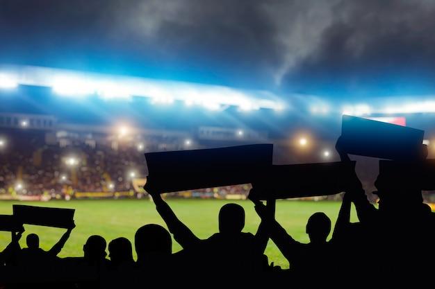 Группа футбольных фанатов на трибуне, вид сзади