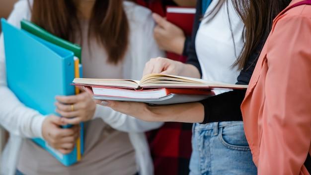 4명의 매력적인 아시아 대학생 그룹이 야외 대학 캠퍼스에서 일하고 공부하는 문서를 들고 함께 서 있습니다. 교육, 우정, 대학생들의 삶에 대한 개념.