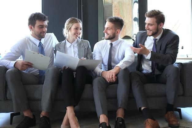 소파에 앉아 4명의 비즈니스 사람들의 그룹입니다. 그들은 함께 일하는 것이 더 행복할 수 없습니다.